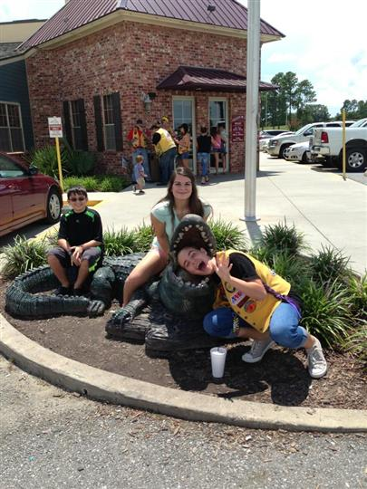 three people posing with a fake alligator