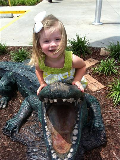 little girl sitting on a fake alligator