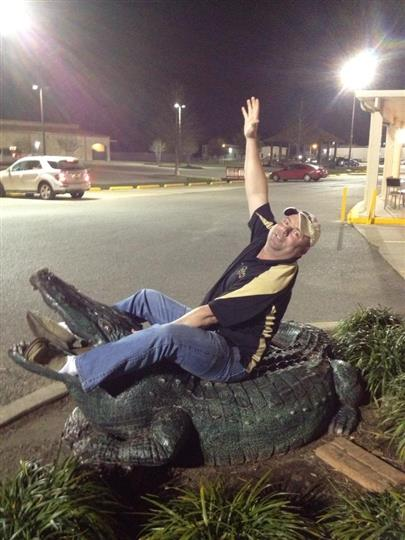 man sitting on a fake alligator