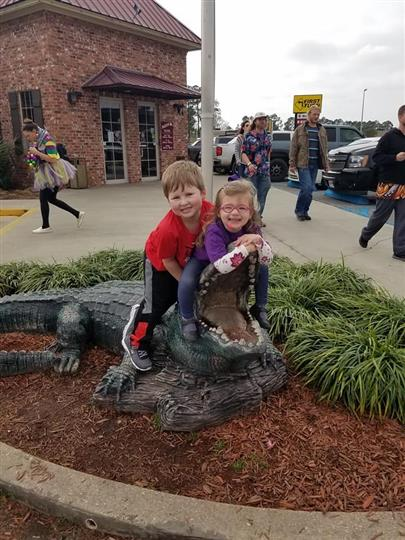 little boy and girl posing with fake alligator