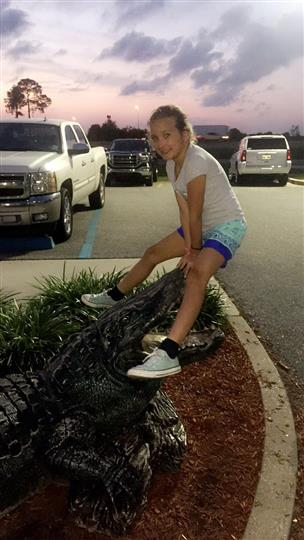 girl posing with fake alligator