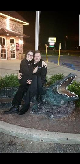 man and woman posing with fake alligator