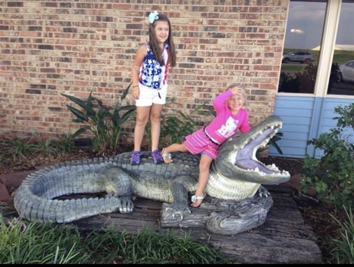 two little girls posing with fake alligator