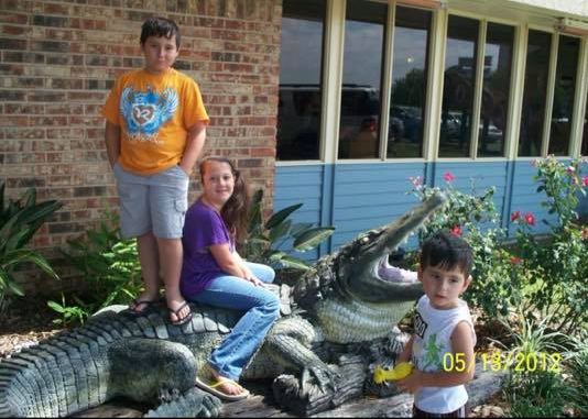 three children posing with fake alligator