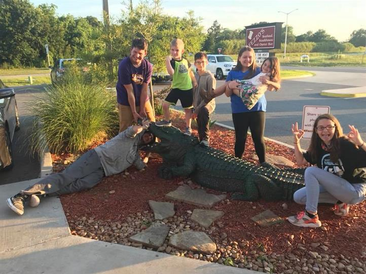 group of kids posing with fake alligator