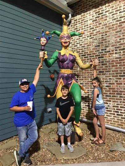 three children posing outside of mardi gras statue