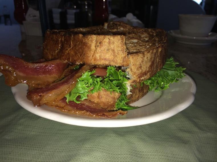 Thick sandwich with bacon, lettuce, tomato on white dish