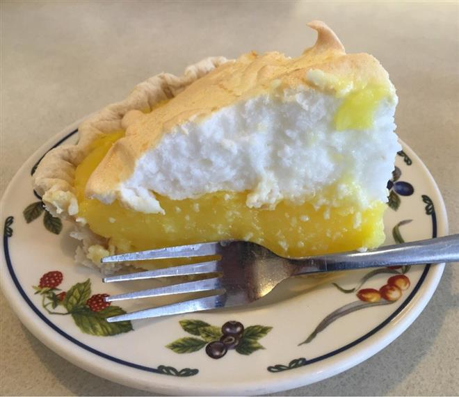 Lemon meringue pie slice on fancy dish
