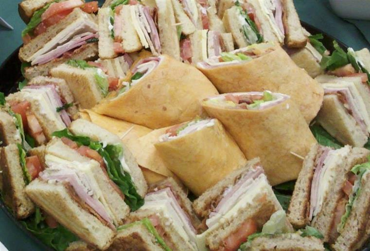 catering display of sliced sandwiches and wraps stacked together