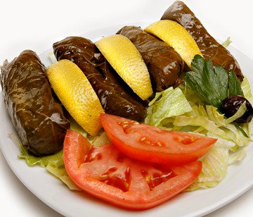 Grape leaves with lemon wedges and a side of tomatoes
