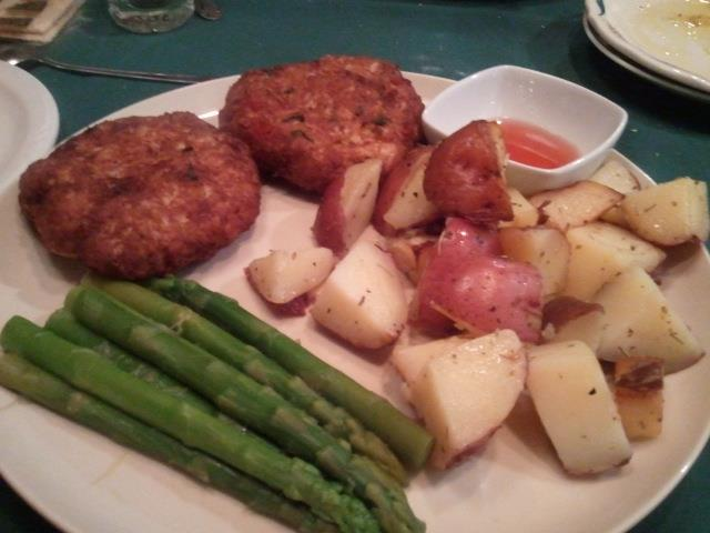 beef patties with a side of cooked potatoes and asparagus