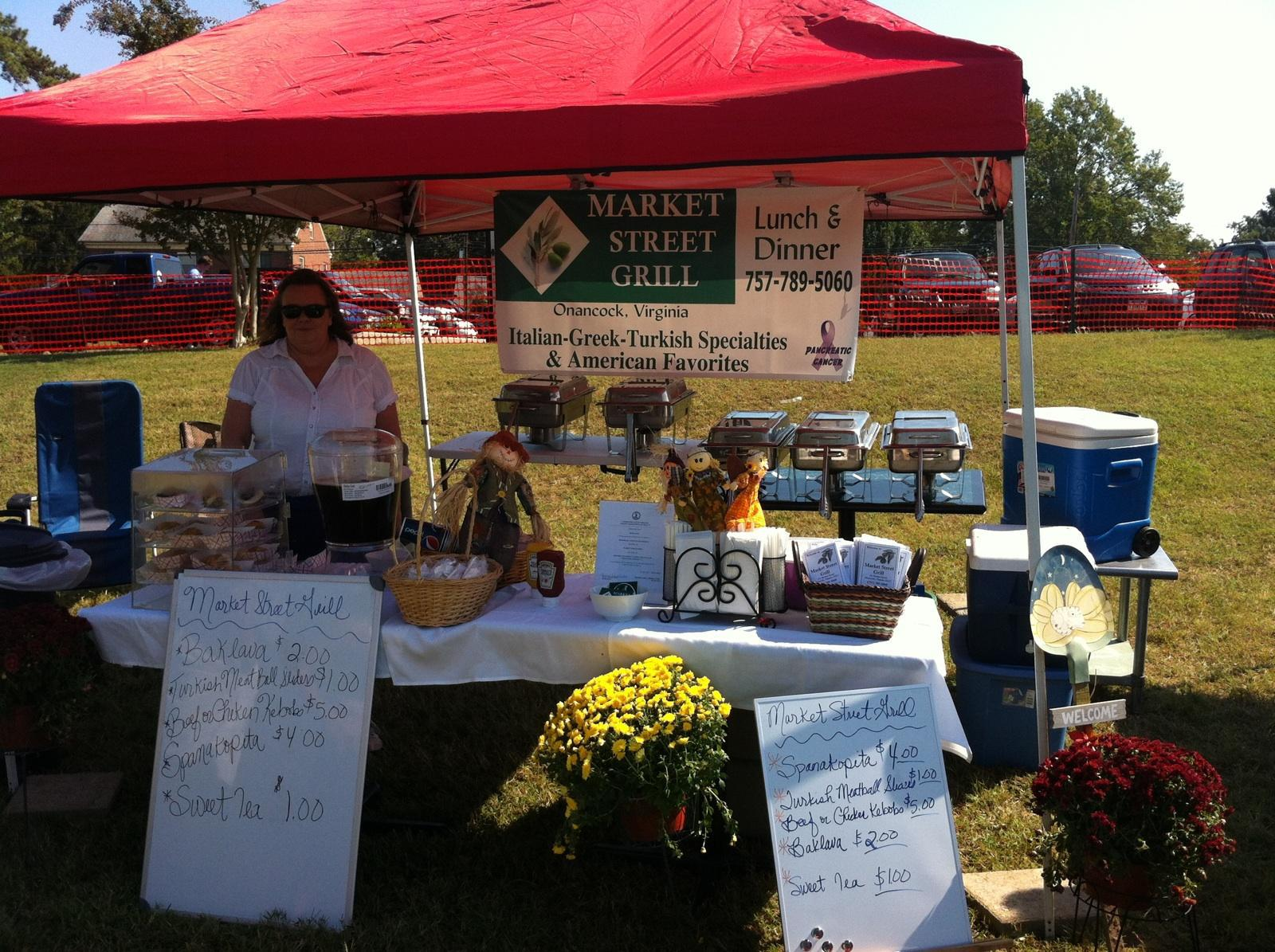 outdoor farmers market stand selling food under a tent
