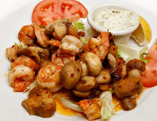 mushrooms and shrimp on a plate with a slice of tomato