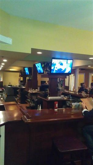 angle of bar with three tv's and customers sitting around the bar