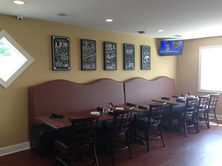 tables with half booth and half chairs with signs on the wall and tv in the corner