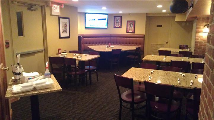 Set tables in the restaurant and a table with cleaning supplies and rolled silverwear