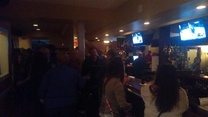 customers standing in front of the bar with bartenders and TVs