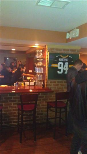 Customers standing in front of the bar with bartenders behind the bar