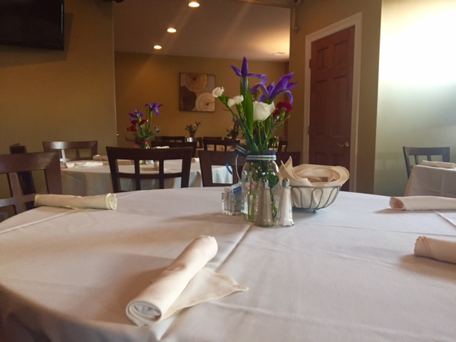 round tables and chairs in the dining room with table cloths and flowers