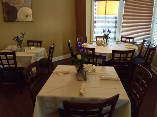 tables with table cloths and chairs with flowers