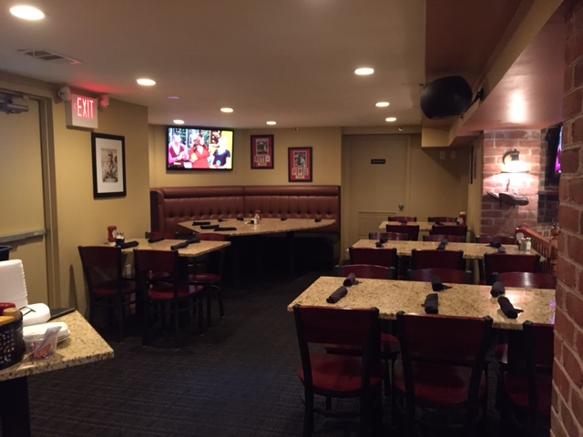 tables and chairs in dining room with a booth in the back below a tv on the wall