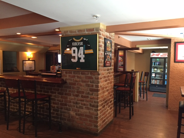 Bar with jersey framed on brick wall with fridge in the background