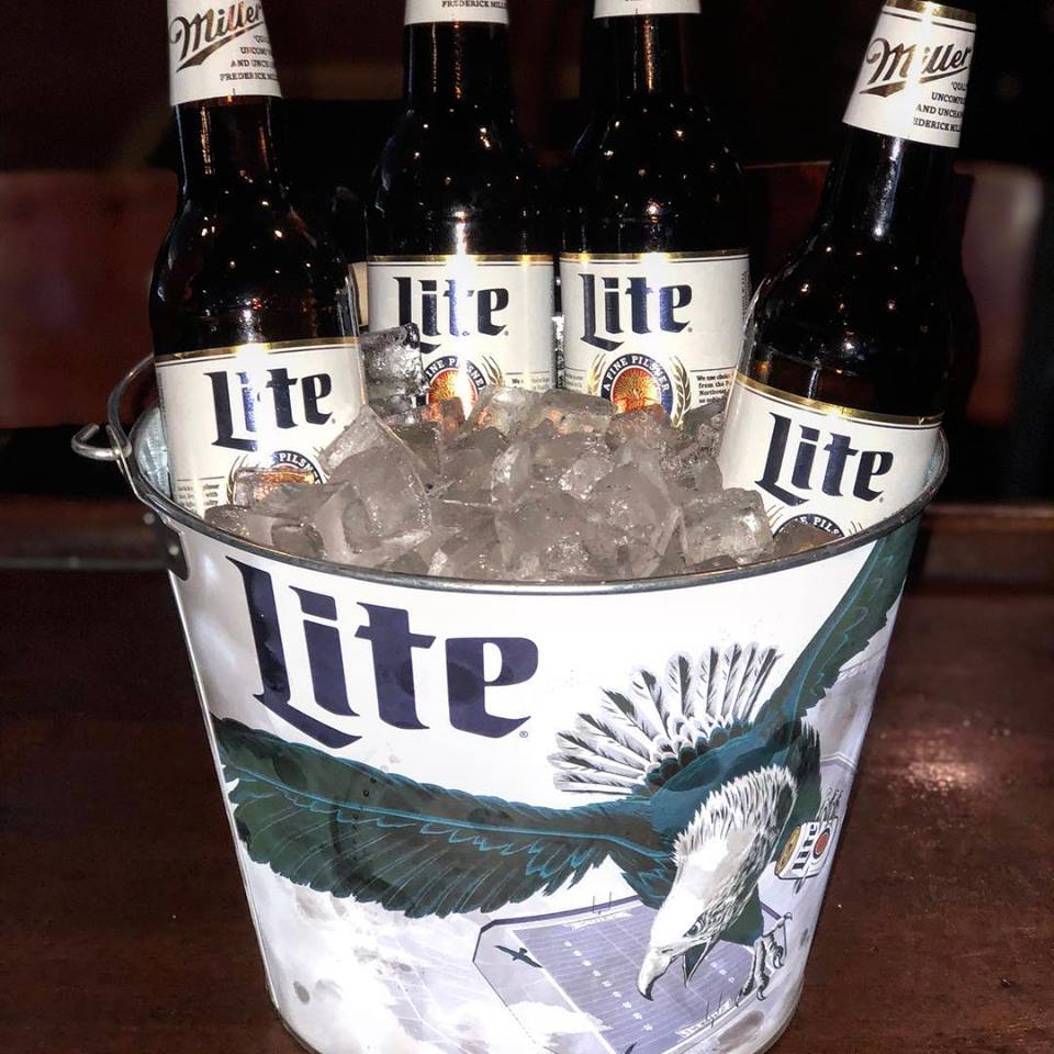 Bucket full of ice with four Miller Lites