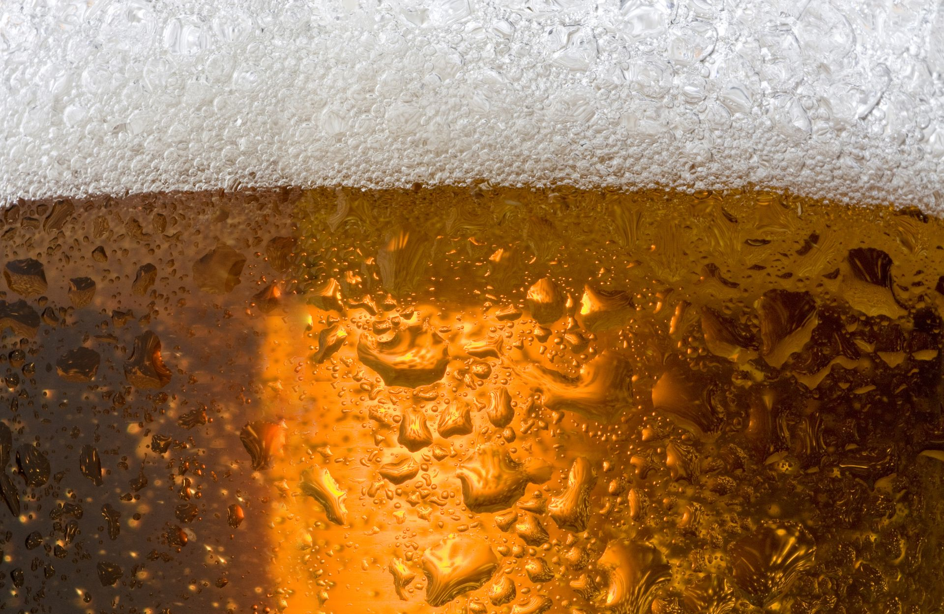 Close up of a glass of beer with foam and condensation on the outside
