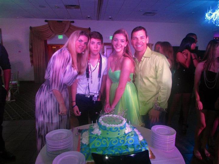 four people smiling in front of birthday cake