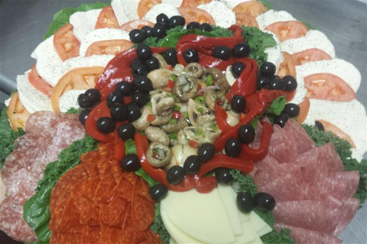 Platter of deli meats and cheeses along with vegetables