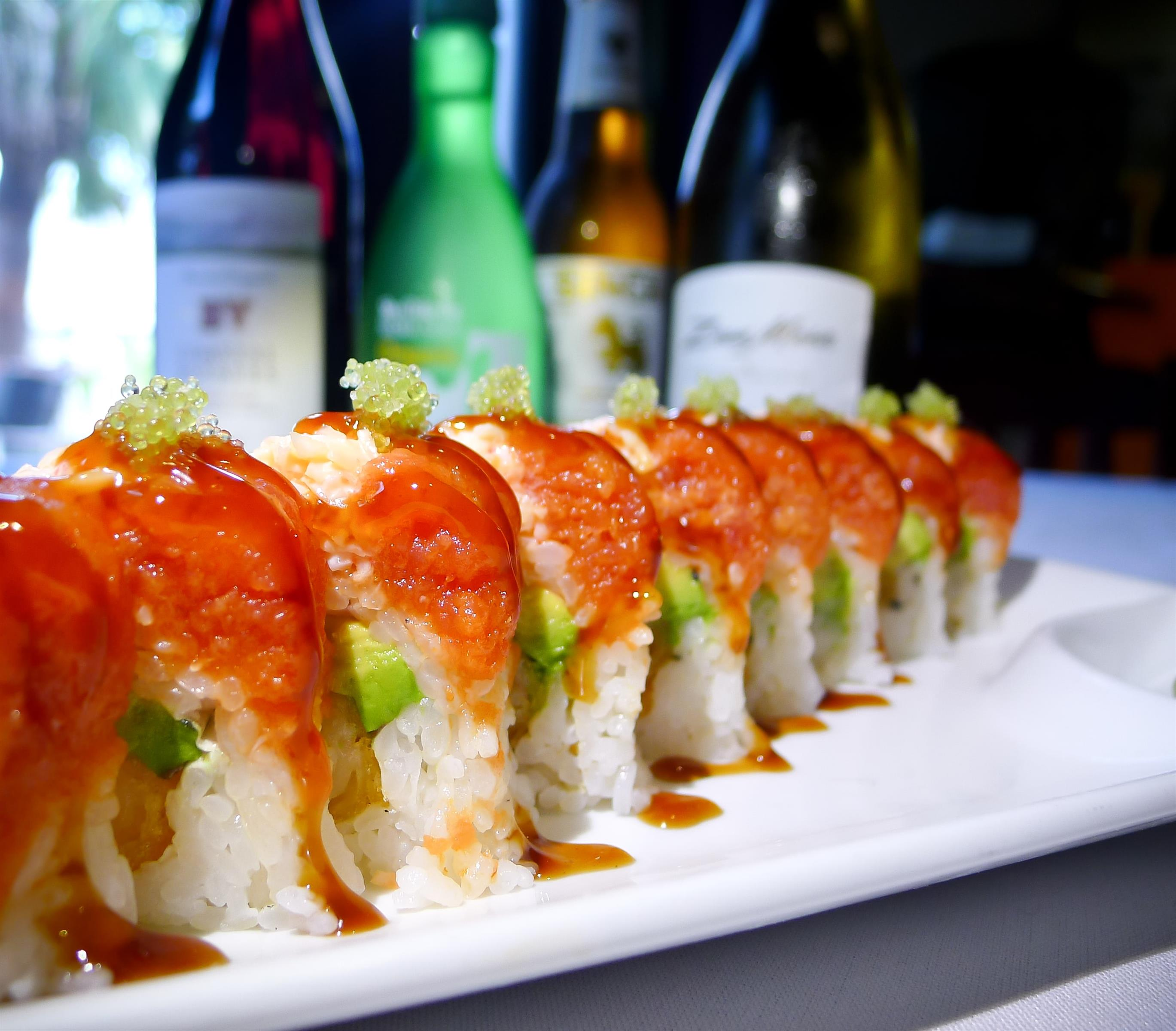 Sushi lined up on white plate covered in orange sauce in front of glass bottles