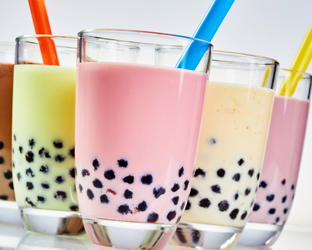 Multiple glasses of bubble tea with pink and yellow drinks with gelatin bubbles at the bottom of the drinks with colorful straws