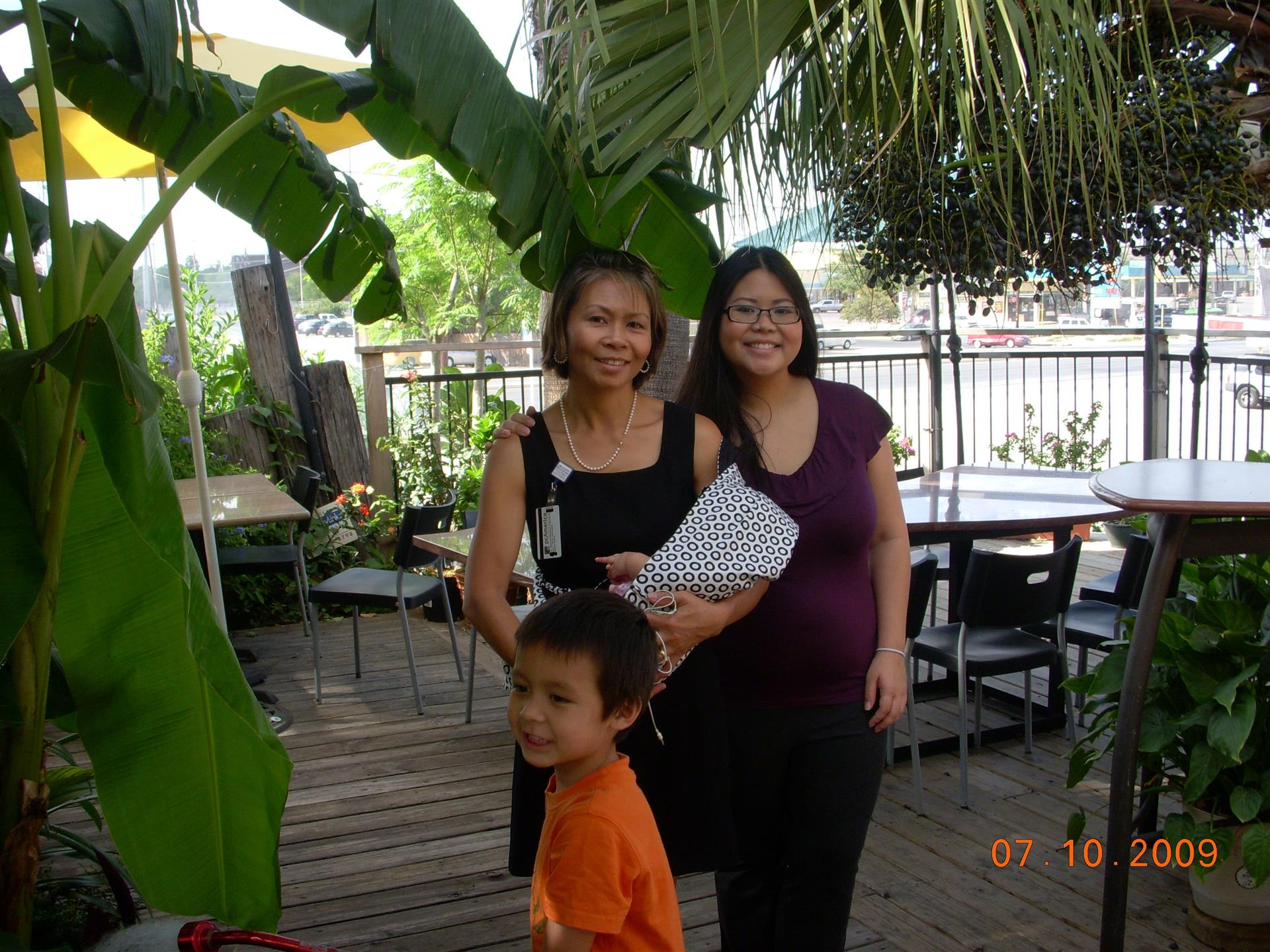 Two females and a child posing for picture on outdoor deck