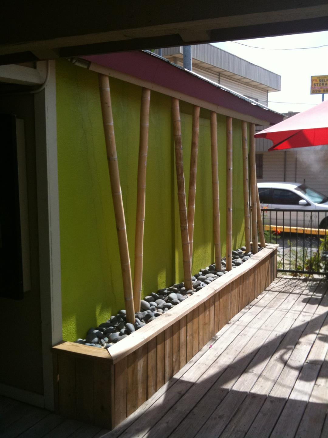Outdoor deck with bamboo supports in rock bed
