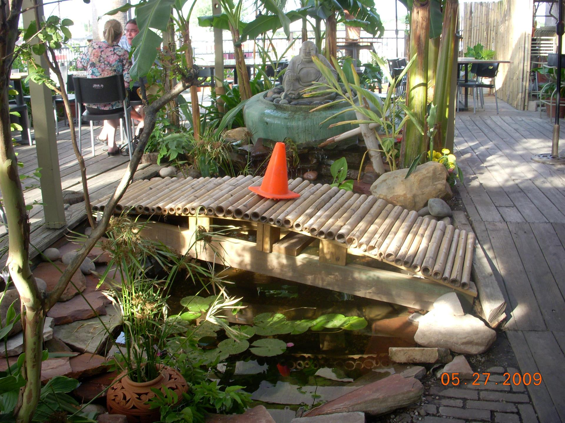Outdoor deck with small bamboo bridge with orange cone in the middle