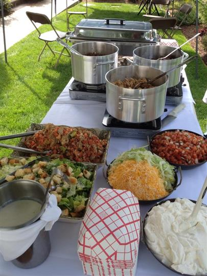 An outdoor catering buffet with hot dishes