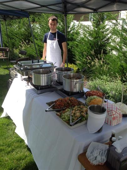 An outdoor catering buffet with hot dishes and a chef posing for a photo