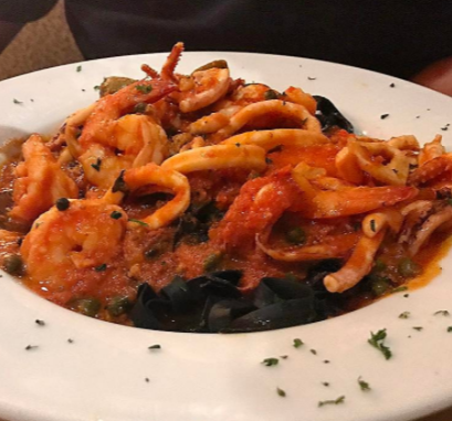 Squid ink pasta with shrimp and calamari in tomato sauce