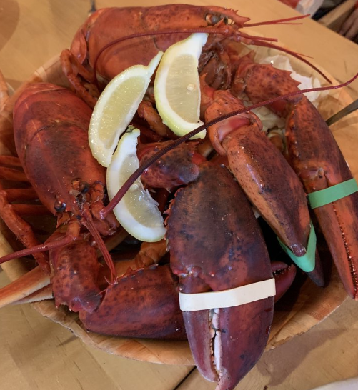 Steamed whole lobster with lemon wedges