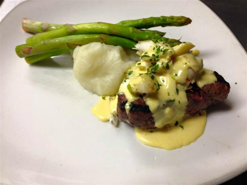 Steak with specialty sauce accompanied by mashed potatoes and asparagus