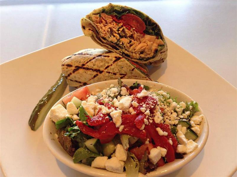 Salad with feta cheese served with a pickle slice and a wrap
