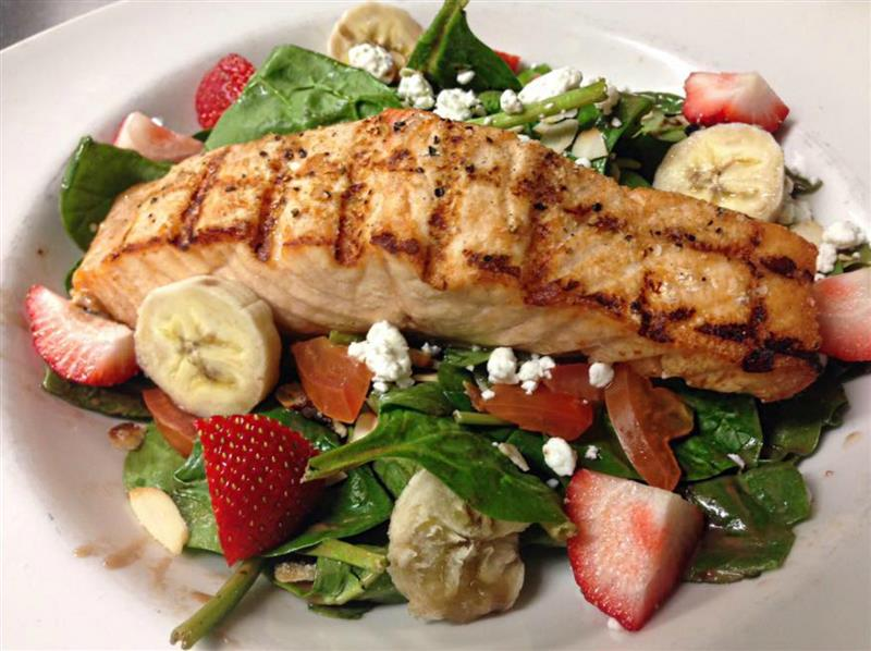 Grilled chicken topped on salad with bananas and strawberries