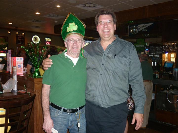 two happy men, one is wearing a green bishop hat with a shamrock on it