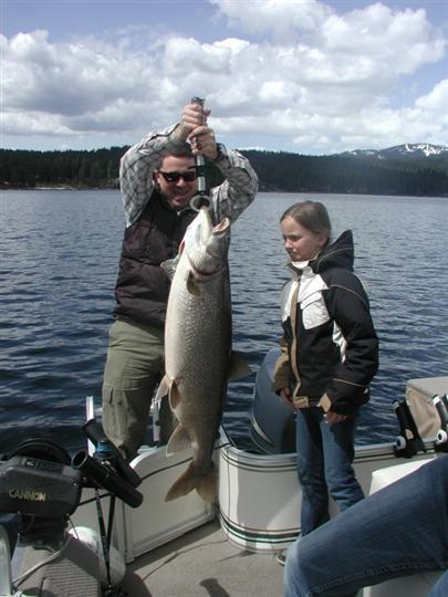 A man and a young girl posing with the big fish they caught