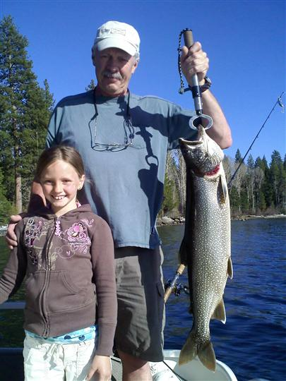 An old man with a young girl posing with a big fish