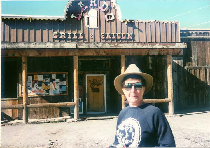 A woman with a hat posing for a photo outside Lardo's Grill & Saloon