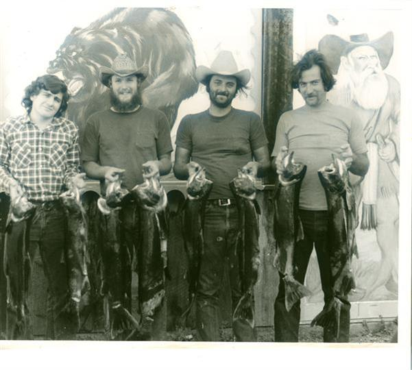A black and white photo of four men holding the fish they caught