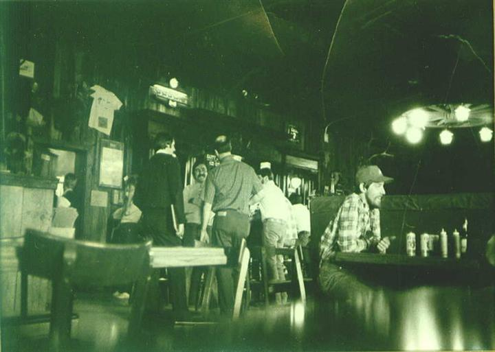 A black and white interior picture of Lardo's Grill & Saloon with people