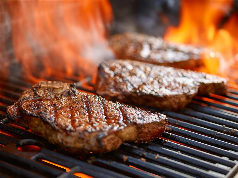 steaks on a flaming grill