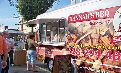 woman placing an order at the window of hannah's bbq food truck parked in the street